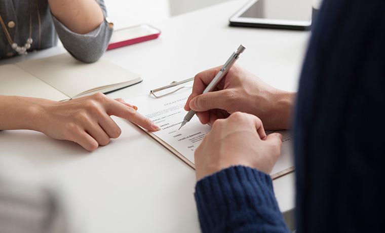 Bancário e cliente a verificar os documentos necessários para crédito habitação